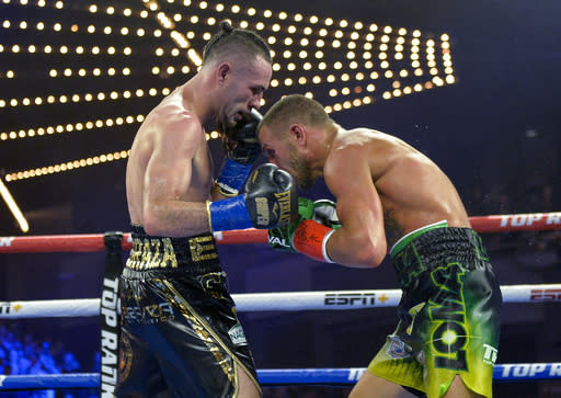 Vasiliy Lomachenko right, tries to tries to avoid a punch from Jose Pedraza in the WB lightweight title boxing match at Madison Square Garden, Saturday, Dec. 8, 2018, in New York. (AP Photo/Howard Simmons)