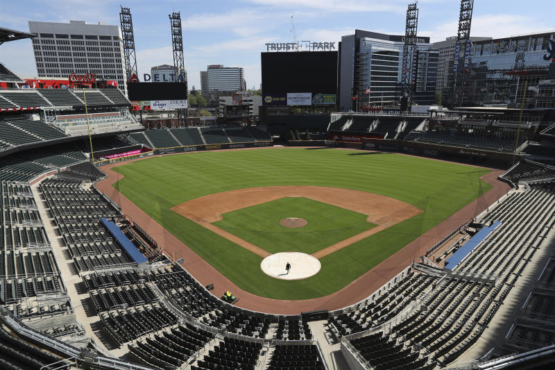 Atlanta Braves field manager Tyler Lenz walks across the covered home plate while maintaining the quality of the field in the team's newly renamed Truist Park, Wednesday, April 1, 2020, in Atlanta. The Braves were scheduled to host their home-opener this Friday, but the season's start was postponed by Major League Baseball because of the coronavirus pandemic. A basic crew is keeping the quality of the field up to playing conditions. (Curtis Compton/Atlanta Journal-Constitution via AP)