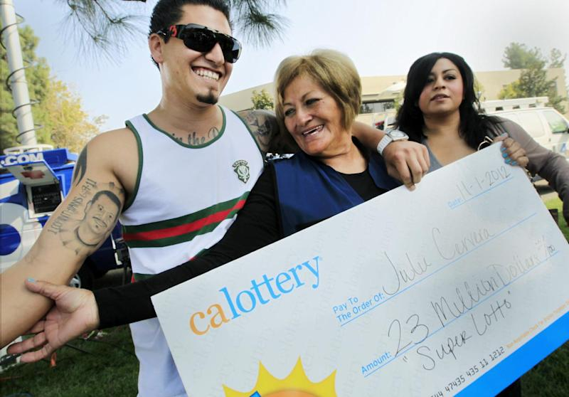Lottery winner Julie Cervera, center, looks at her recently dead son pictured on a tattoo, as she is hugged by her grandson Rudy Ray, left, and daughter Charliena Marquez, right, after a news conference in San Bernardino, Calif., Friday, Nov. 2, 2012. The 69-year-old California grandmother came forward to claim a $23 million lottery jackpot after the winning ticket languished in her car's glove compartment for months and almost expired. With 180 days to claim the prize, Cervera only had until Nov. 25 to cash in. (AP Photo/Damian Dovarganes)