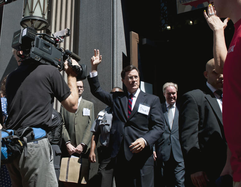 Comedian Stephen Colbert waves as he exits the Federal Election Commission in Washington, Thursday, June 30, 2011, after attending a hearing on his request to form a political action committee. (AP Photo/Cliff Owen)