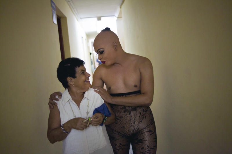 "In this May 11, 2013, Abrahan Bueno, 39, a gay transvestite artist known as ""Imperio,"" chats with the woman in charge of the dressing rooms at the Karl Marx theater in Havana, Cuba. A week of drag shows, colorful marches and social and cultural events in Havana culminates Friday with celebrations of the International Day Against Homophobia. Gays were persecuted for decades after the 1959 Cuban Revolution, sometimes sent to grueling rural work camps along with others considered socially suspect by the Communist government. But there has been a gradual shift away from macho attitudes, and Fidel Castro himself has publicly regretted the mistreatment of people seen as different. (AP Photo/Ramon Espinosa)"