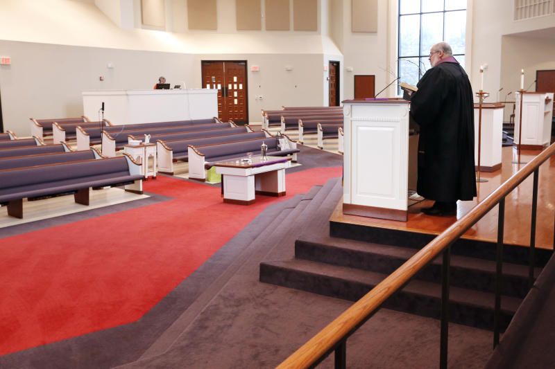 FILE - In this Sunday, March 15, 2020 photo, Rev. Kip Rush delivers his sermon in a sanctuary filled with mostly empty pews during a service at Brenthaven Cumberland Presbyterian Church in Brentwood, Tenn. The church decided to broadcast the service instead of holding a service with the entire congregation because of the COVID-19 coronavirus. (AP Photo/Mark Humphrey)