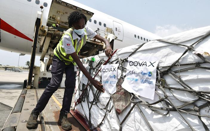 A woman puts Covax stickers as workers unload a shipment of AstraZeneca Covid-19 vaccine from a plane at Felix Houphouet Boigny airport of Abidjan - AFP