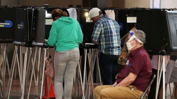 PHOTO: Voters fill out their ballots as they vote at the Stephen P. Clark Government Center polling station on Oct. 19, 2020, in Miami. (Joe Raedle/Getty Images)