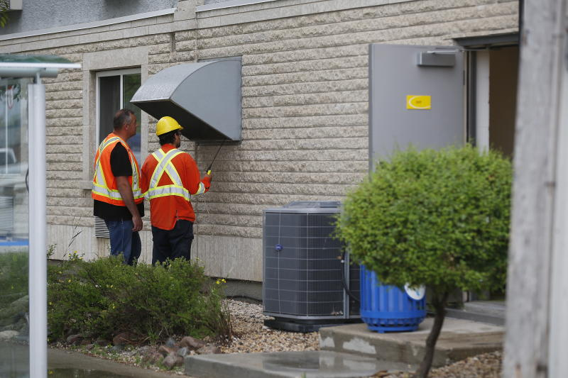 Gas workers check air quality at ventilation vents after emergency personnel were called to a gas leak at a Super 8 hotel in Winnipeg Tuesday, July 9, 2019. Forty six people were taken to emergency hospitals. THE CANADIAN PRESS/John Woods