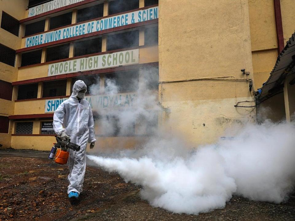 A school in Mumbai is fumigated against Covid-19  (EPA)