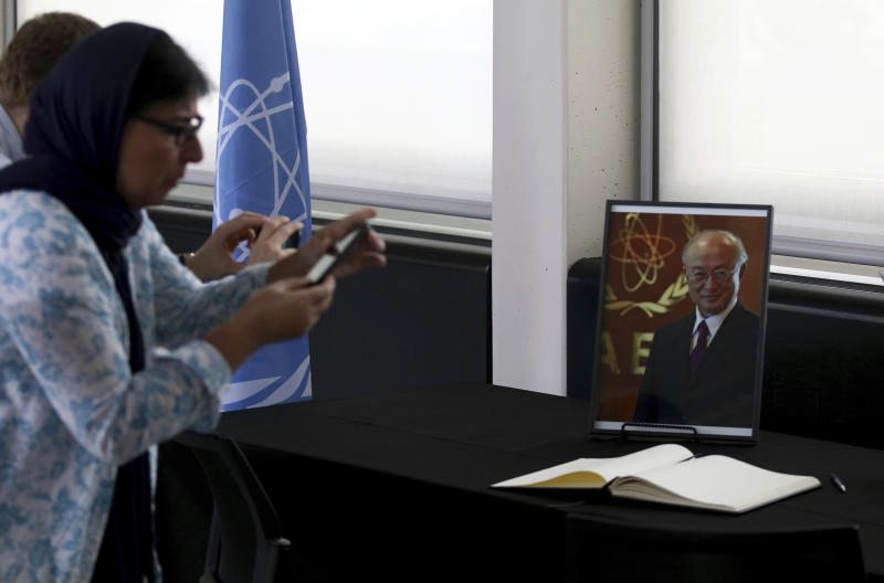 People take a pictures of the condolence book and a portrait photo of Director General of the International Atomic Energy Agency, IAEA, Yukiya Amano from Japan in Vienna, Austria, Monday, July 22, 2019. The IAEA announced the death of the agency's Director General Yukiya Amano at the age of 72 years. (AP Photo/Ronald Zak)