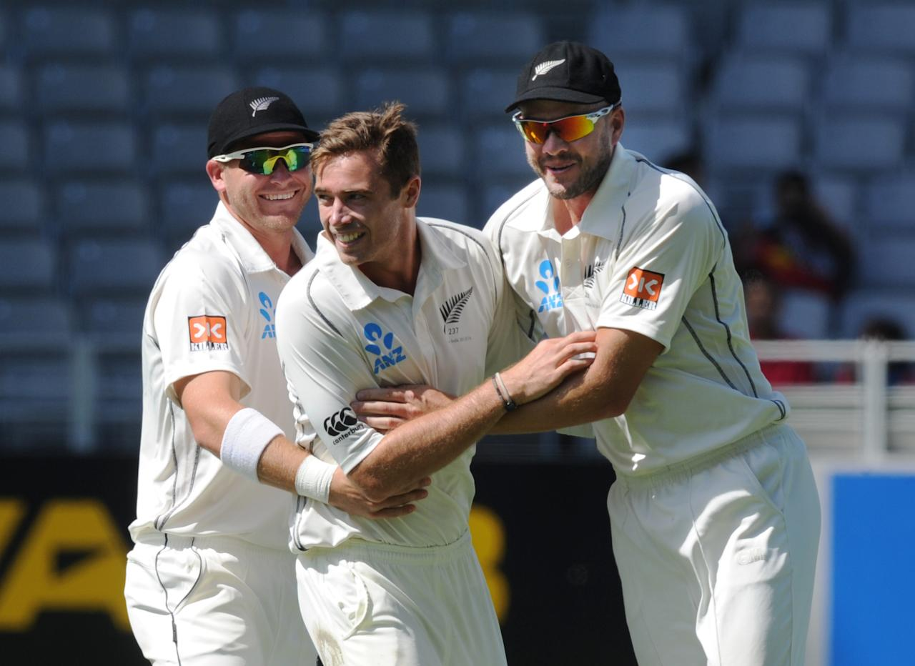 New Zealand's Tim Southee, center, with Corey Anderson, left and Peter Fulton after dismissing India's Rohit Sharma for 19 on the fourth day of the first cricket test, at Eden Park in Auckland, New Zealand, Sunday, Feb. 9, 2014. (AP Photo/SNPA, Ross Setford) NEW ZEALAND OUT