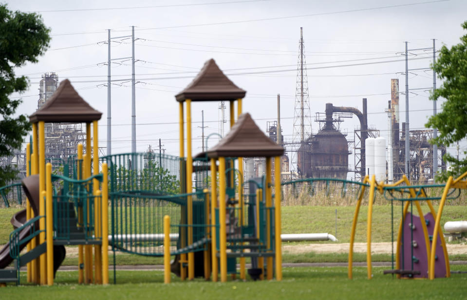 FILE - In this Monday, March 23, 2020 file photo, a playground outside the Prince Hall Village Apartments sits empty near one of the petrochemical facilities in Port Arthur, Texas. According to a study published Wednesday, April 28, 2021 in the journal Science Advances, across America, people of color are disproportionately exposed to air pollution from industry, vehicles, construction and many other sources. (AP Photo/David J. Phillip)