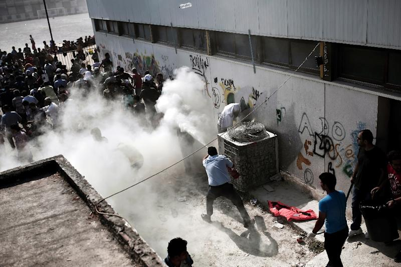 Kos policemen try to disperse hundreds of migrants by spraying them with fire extinguishers during a gathering for a registration procedure on August 11, 2015 (AFP Photo/Angelos Tzortzinis)