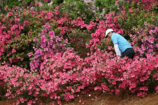 """World number one Rory McIlroy, playing a shot out of the flowers on the 13th hole at Augusta National, says a Masters in October would be """"pretty cool"""""""