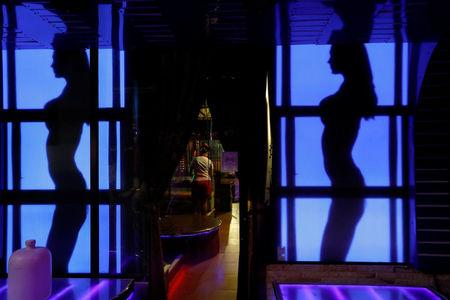 A woman stands inside a go-go bar before they open for customers in Pattaya