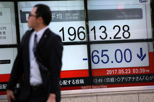 <p>A man walks past an electronic stock board showing Japan's Nikkei 225 index at a securities firm Tuesday, May 23, 2017, in Tokyo. Asian shares meandered Tuesday after a strong overnight lead from Wall Street was vanquished by an explosion in Manchester, England. (AP Photo/Eugene Hoshiko) </p>