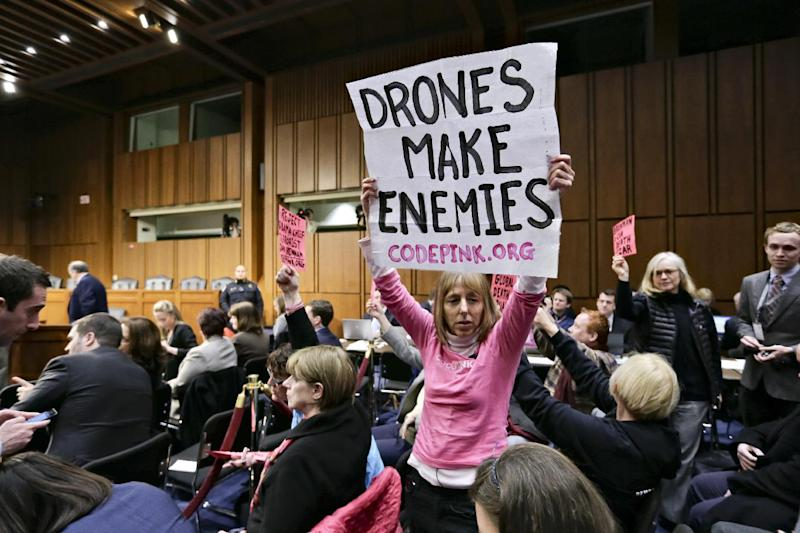 Protesters from CODEPINK, a group opposed to U.S. militarism, including co-founder Medea Benjamin, center, disrupt the start of the Senate Intelligence Committee confirmation hearing for John Brennan, Thursday, Feb. 7, 2013, on Capitol Hill in Washington. (AP Photo/J. Scott Applewhite)