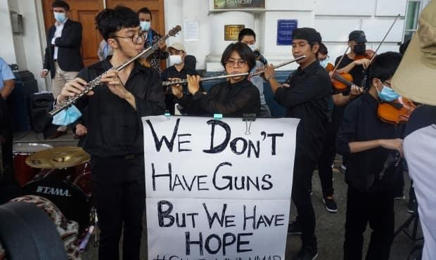 Musicians perform outside the British embassy during a demonstration against the military coup in Yangon on Friday, Feb. 19, with a sign reading 'We don't have guns but we have hope.'