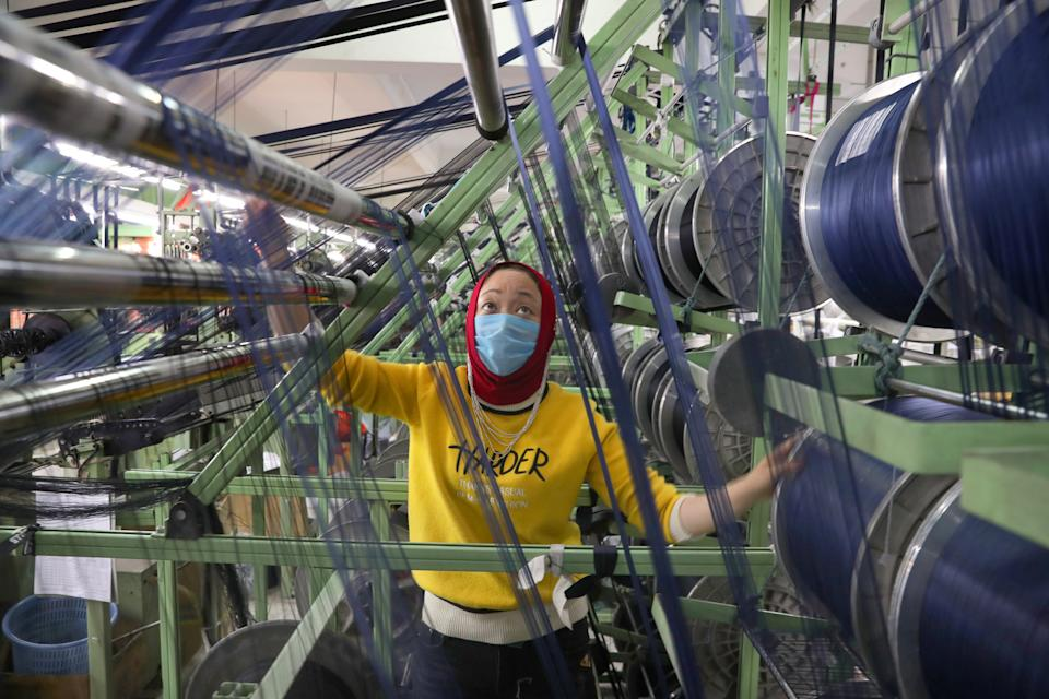 An ethnic minority employee wearing a face mask works on a production line manufacturing elastic fabric products, as the country is hit by an outbreak of the novel coronavirus disease (COVID-19), in Nantong, Jiangsu province, China March 26, 2020. China Daily via REUTERS ATTENTION EDITORS - THIS IMAGE WAS PROVIDED BY A THIRD PARTY. CHINA OUT.