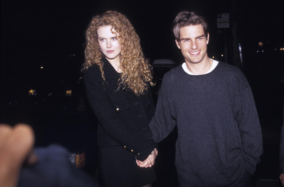 Nicole Kidman and Tom Cruise hold hands while walking outdoors in Paris in September 1993