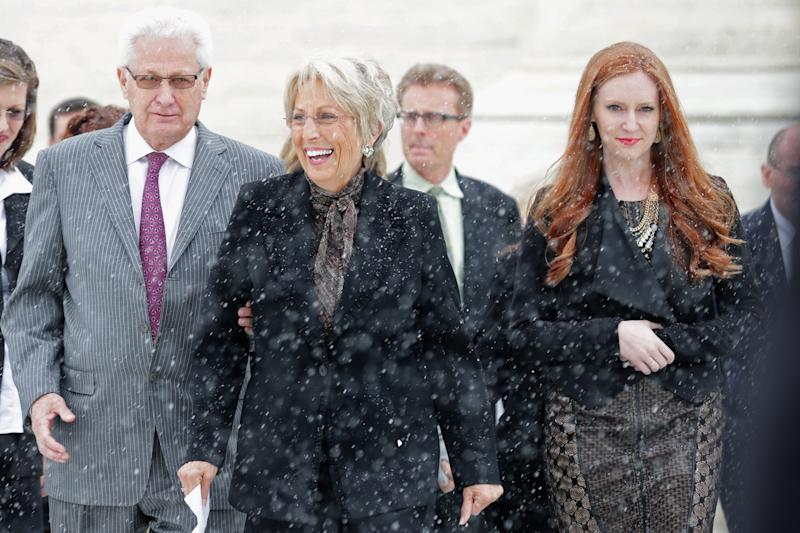 Hobby Lobby co-founders David Green (L) and Barbara Green (C) leave the U.S. Supreme Court on March 25, 2014 in Washington, DC