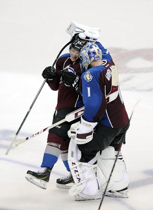 Colorado Avalanche goalie Semyon Varlamov, right, of Russia, congratulates Avalanche center Nathan MacKinnon, left, after MacKinnon scored the game-winning goal in overtime in Game 5 of an NHL hockey first-round playoff series against the Minnesota Wild on Saturday, April 26, 2014, in Denver. The Avalanche won 4-3. (AP Photo/Chris Schneider)