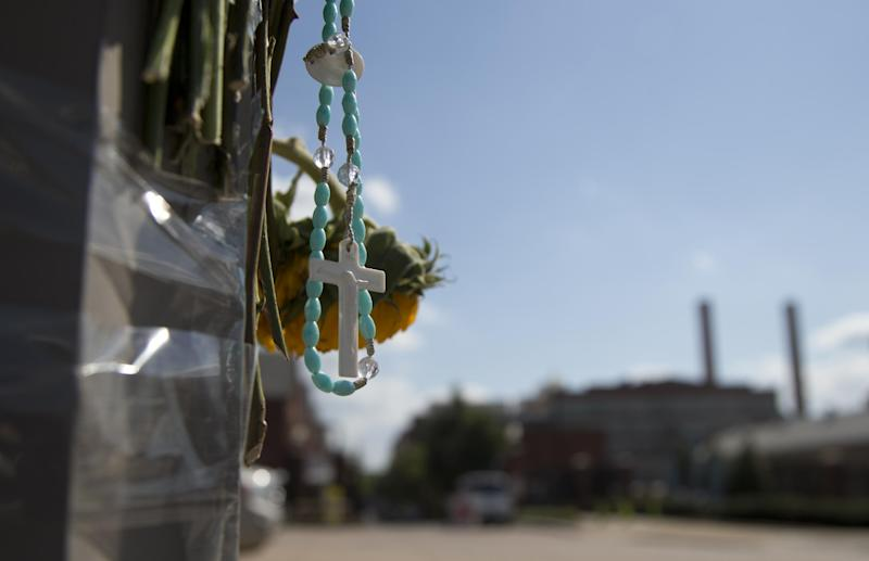 A rosary hangs from a makeshift memorial on a lamp post across the street from the Washington Navy Yard, Friday, Sept. 20, 2013, in Washington. A gunman killed 12 people in the Navy Yard on Monday, Sept. 16, 2013, before being fatally shot in a gun battle with law enforcement. (AP Photo/Carolyn Kaster)