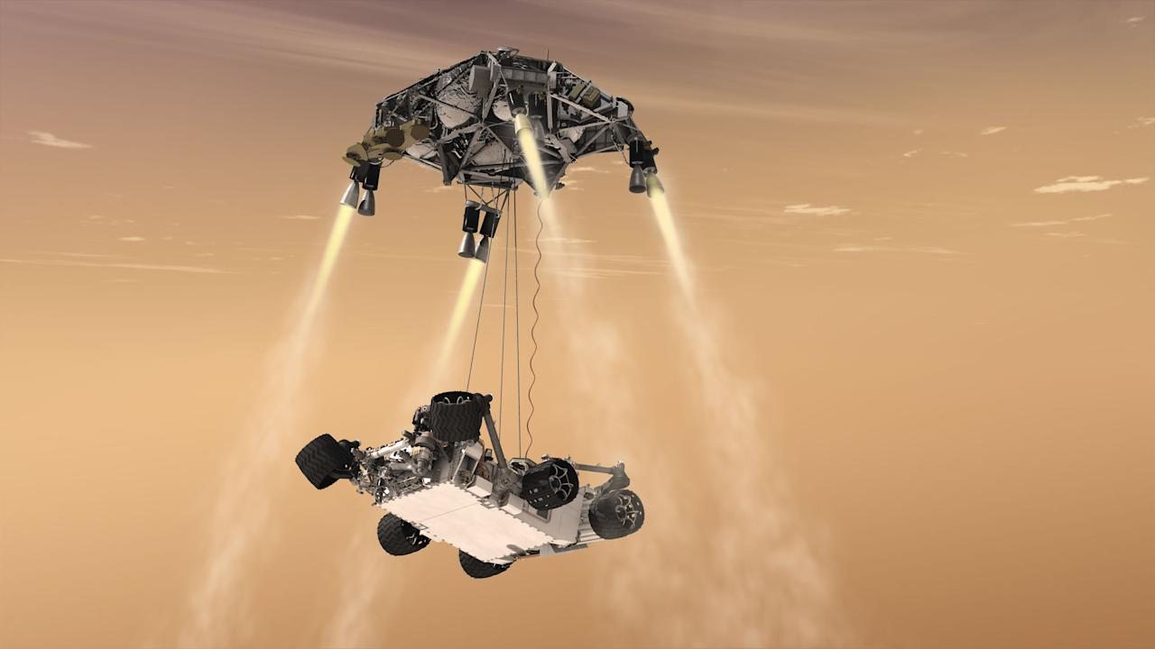 "In this 2011 artist's rendering provided by NASA/JPL-Caltech, a ""sky crane"" lowers the Mars Science Laboratory Curiosity rover onto the surface of Mars. The mobile robot is designed to investigate Mars' past or present ability to sustain microbial life. (AP Photo/NASA/JPL-Caltech)"