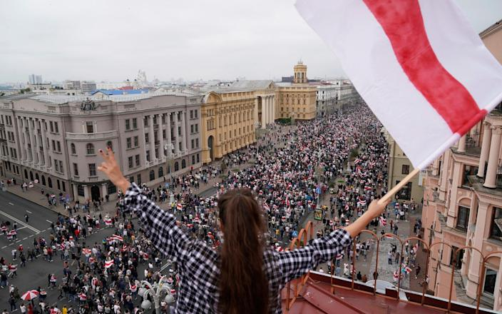 A woman waves an old Belarusian national flag standing on the roof as Belarusian opposition supporters march to Independence Square in Minsk, Belarus - Evgeniy Maloletka/AP