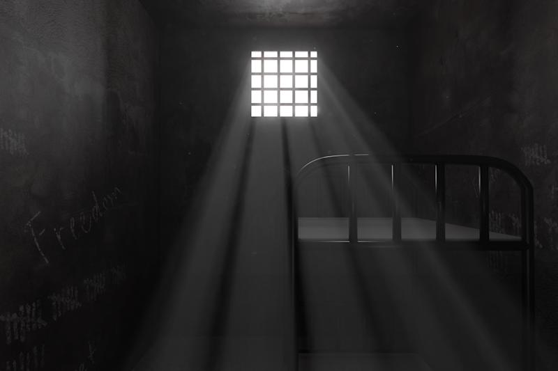 3d rendering of grunge prison cell with bunk bed and light ray of window