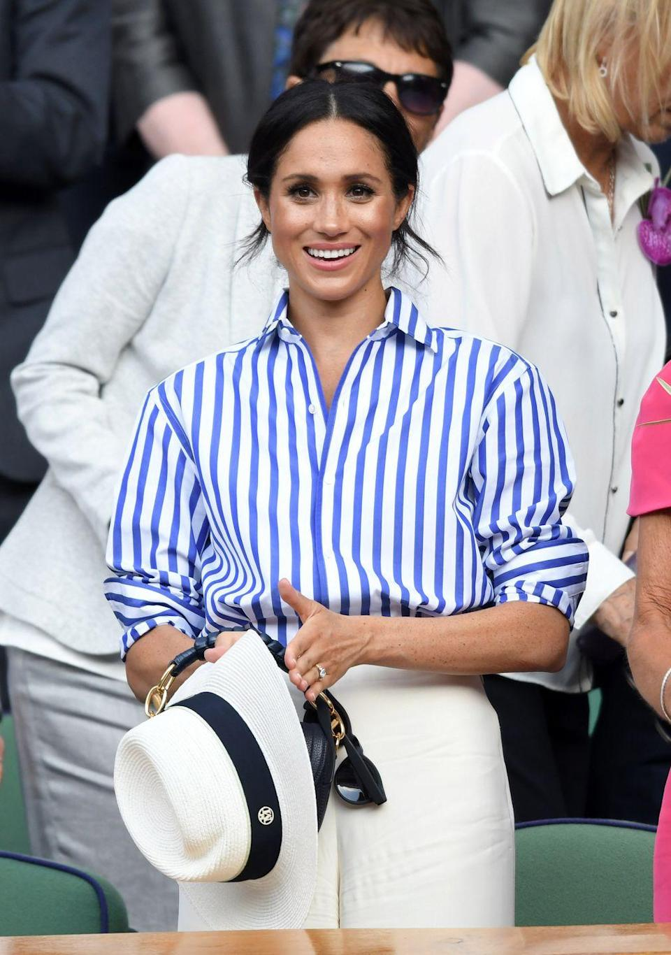 <p>The newlywed wore a classic blue-striped button-down shirt and crisp white wide-leg trousers from Ralph Lauren to Wimbledon, July 2018. </p>