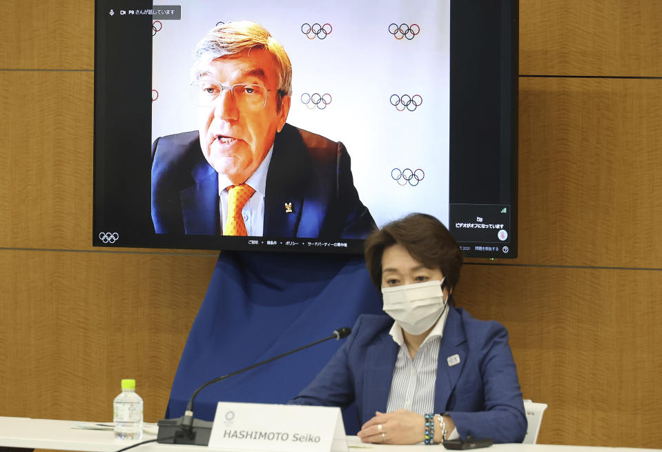 International Olympic Committee (IOC) President Thomas Bach delivers an opening speech on a screen at a meeting of the IOC Coordination Commission for the Tokyo 2020 Olympics in Tokyo on Wednesday, May 19, 2021, while Tokyo 2020 Olympics organizing committee President Seiko Hashimoto listens. Bach, Hashimoto, Japanese Olympic Minister Tamayo Marukawa and Tokyo Gov. Yuriko Koike attended a three-day meeting. (Yoshikazu Tsuno/Pool Photo via AP)