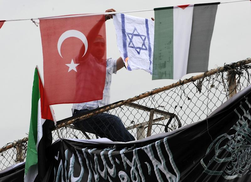 A demonstrator burns an Israeli flag as he sits between Turkish (L) and Palestinian flags during a protest against Israel on June 5, 2010 in Istanbul (AFP Photo/Bulent Kilic)