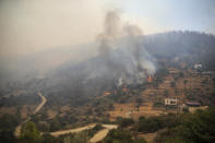 The smoke-engulfed Mazi area engulfed by wildfires, forcing people to be evacuated, in Bodrum, Mugla, Turkey, Sunday, Aug. 1, 2021. More than 100 wildfires have been brought under control in Turkey, according to officials. The forestry minister tweeted that five fires are continuing in the tourist destinations of Antalya and Mugla. (AP Photo/Emre Tazegul)