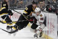 Boston Bruins right wing David Backes (42) checks Chicago Blackhawks defenseman Dennis Gilbert (39) into the boards in the second period of an NHL hockey game, Thursday, Dec. 5, 2019, in Boston. (AP Photo/Elise Amendola)