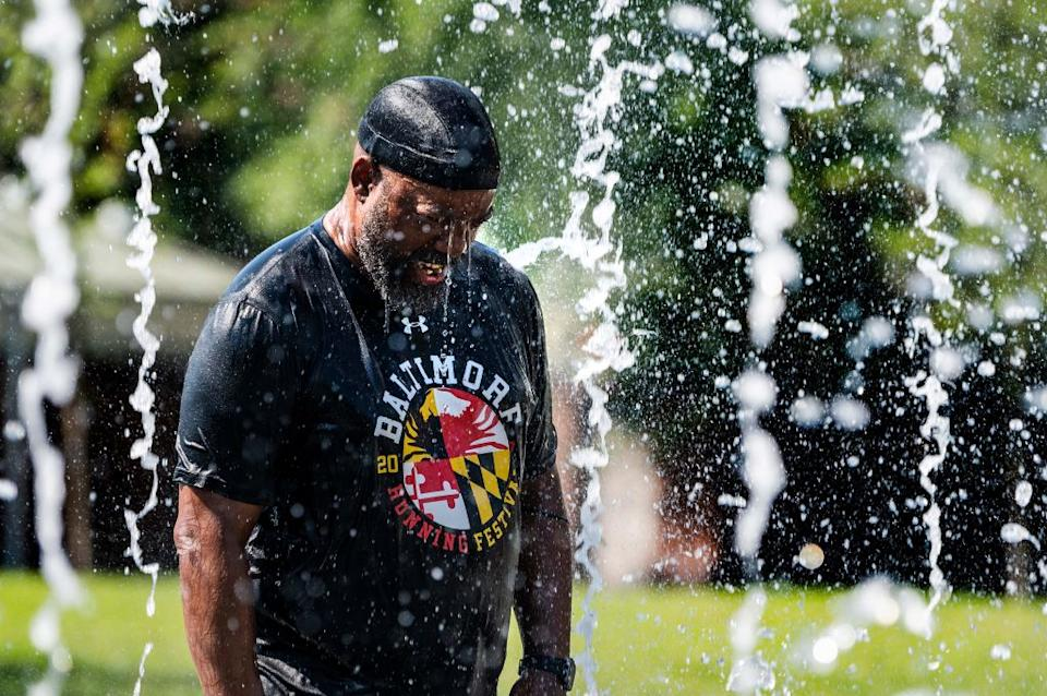 A man cools off in a fountain at Inner Harbor in Baltimore, Maryland.