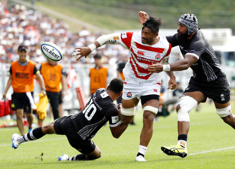 Amanaki Lelei Mafi, center, is tackled by Fiji's Ben Volavola, left, during a Pacific Nations Cup rugby match at Kamaishi Recovery Memorial Stadium in Kamaishi, northern Japan, Saturday, July 27, 2019. Japan took big step forward in Rugby World Cup preparation with a five-try 34-21 win over Fiji in Pacific Nations Cup (Meika Fujio/Kyodo News via AP)