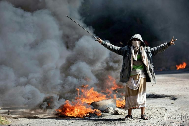 A Yemeni man next to burning tyres during protests calling for the removal of the Saudi-backed coalition government and deteriorating economic and living conditions, in Yemen's third city of Taez on September 27 (AFP/AHMAD AL-BASHA)