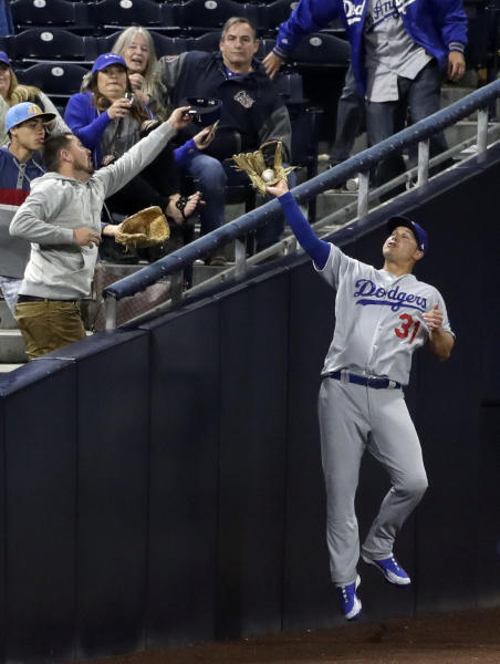 Los Angeles Dodgers left fielder Joc Pederson can't make the catch on a foul ball hit by San Diego Padres' Freddy Galvis during the seventh inning of a baseball game Wednesday, April 18, 2018, in San Diego. (AP Photo/Gregory Bull)