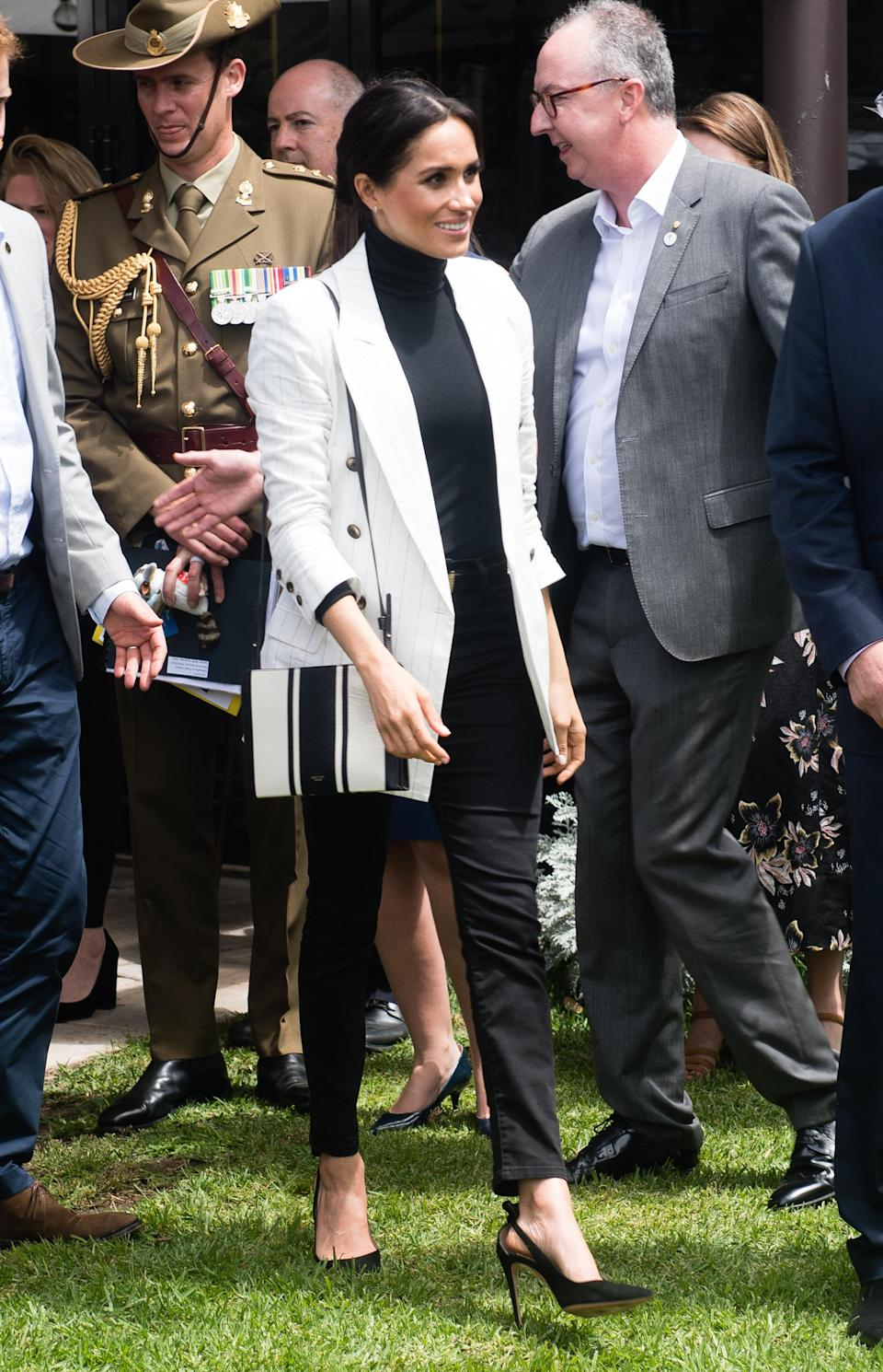 <p>For a reception hosted by the Prime Minister of Australia at The Pavilion Restaurant, Meghan paired her striped Oroton crossbody bag with Aquazzura pumps, a turtleneck, a £510 blazer by L'Agence and go-to £159 Mother Denim jeans. <em>[Photo: Getty]</em> </p>