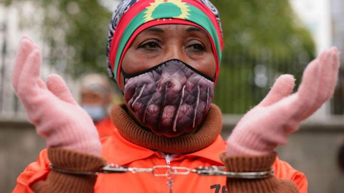 Activists in prison jumpsuits and handcuffs protest human rights abuses against the Oromo people of Ethiopia at a demonstration opposite Downing Street on Whitehall in London, England, on October 10, 2020.