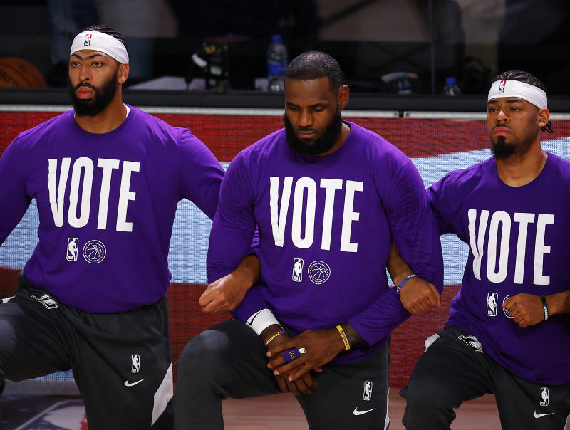 "LeBron James, wearing a ""VOTE"" shirt, kneels and links arms with his teammates during the national anthem."