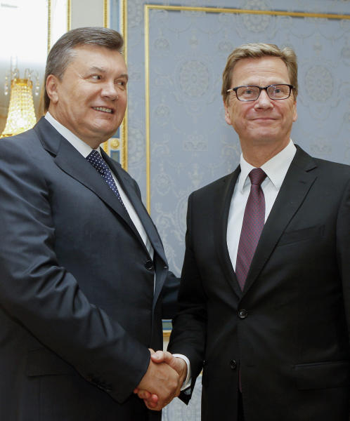 Ukrainian President Viktor Yanukovych, left, welcomes German Foreign Minister Guido Westerwelle, during their meeting in Kiev, Ukraine, Friday, June 21, 2013. Preparations for signing the Association Agreement and European integration will be in the focus of Friday's talks between Ukrainian Foreign Minister Leonid Kozhara and his German counterpart Guido Westerwelle, who has arrived in Kiev on a brief visit. (AP Photo/Sergey Dolzhenko, Pool)