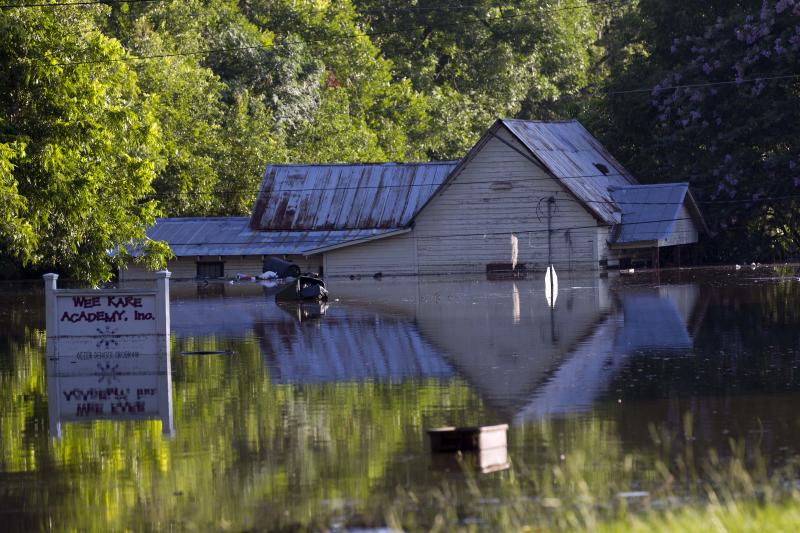 Flood water surrounds homes in Live Oak Fla., Wednesday, June 27, 2012. Dozens of homes and much of the downtown area was flooded by torrential rains from Tropical Storm Debby. (AP Photo/Dave Martin)