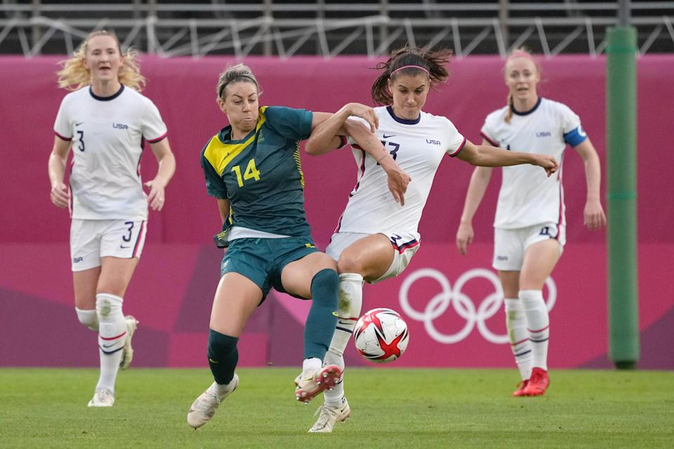 Australia player Alanna Kennedy (14) tries to clear the ball from U.S. player Alex Morgan (13) during the Tokyo Olympics.