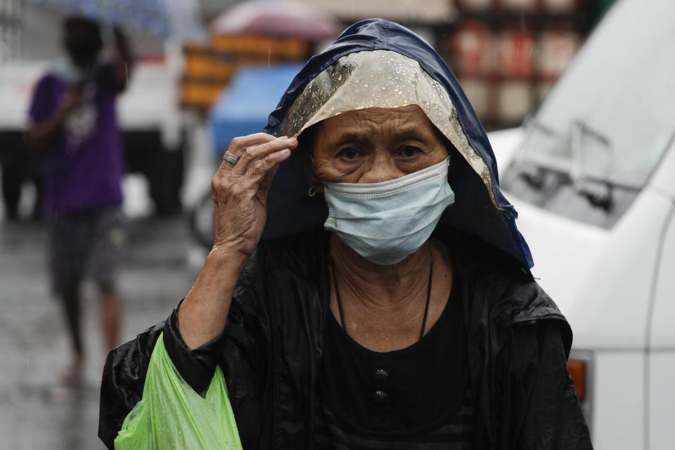 A woman wearing a face mask to prevent the spread of the coronavirus walks as rains from a typhoon locally known as Goni starts in Manila, Philippines on Sunday Nov. 1, 2020. The super typhoon slammed into the eastern Philippines with ferocious winds early Sunday and about a million people have been evacuated in its projected path, including in the capital where the main international airport was ordered closed. (AP Photo/Aaron Favila)
