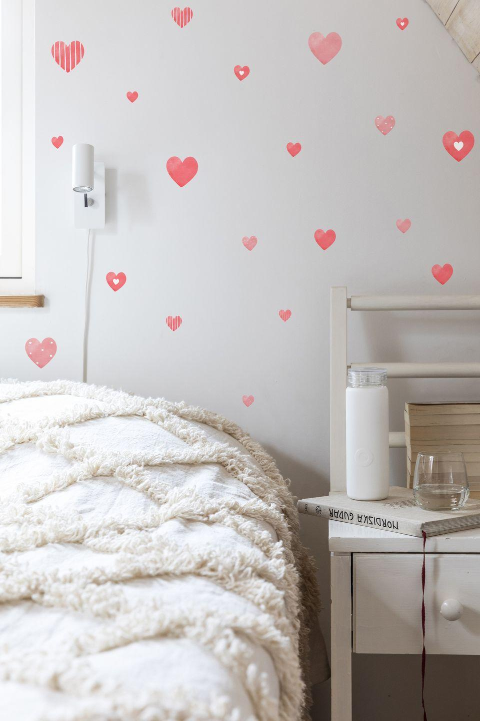 """<p>A really easy way to transform bland walls is with red heart stickers, or similar. It's a great way to create an instant feature wall. These stickers can be positioned and repositioned many times, without leaving any residue behind on wall surfaces.</p><p>Pictured: Reusable Heart Wall Decals, <a href=""""https://www.stickers4walls.co.uk/Reusable_Valentines_Heart_Wall_Stickers/p1294546_20955380.aspx"""" rel=""""nofollow noopener"""" target=""""_blank"""" data-ylk=""""slk:Stickers4Walls"""" class=""""link rapid-noclick-resp"""">Stickers4Walls</a></p>"""