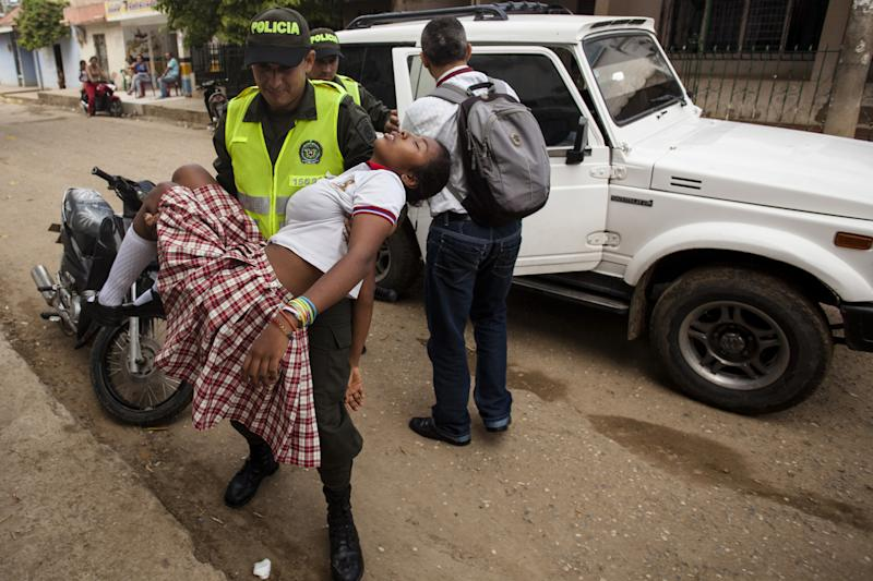 A teenage girl is brought to hospital in Carmen de Bolivar, Bolivar Province, Colombia, after fainting on September 2, 2014