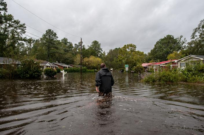 Scott walks through a flooded neighborhood in Lumberton checking homes for any pets that may have been left behind.