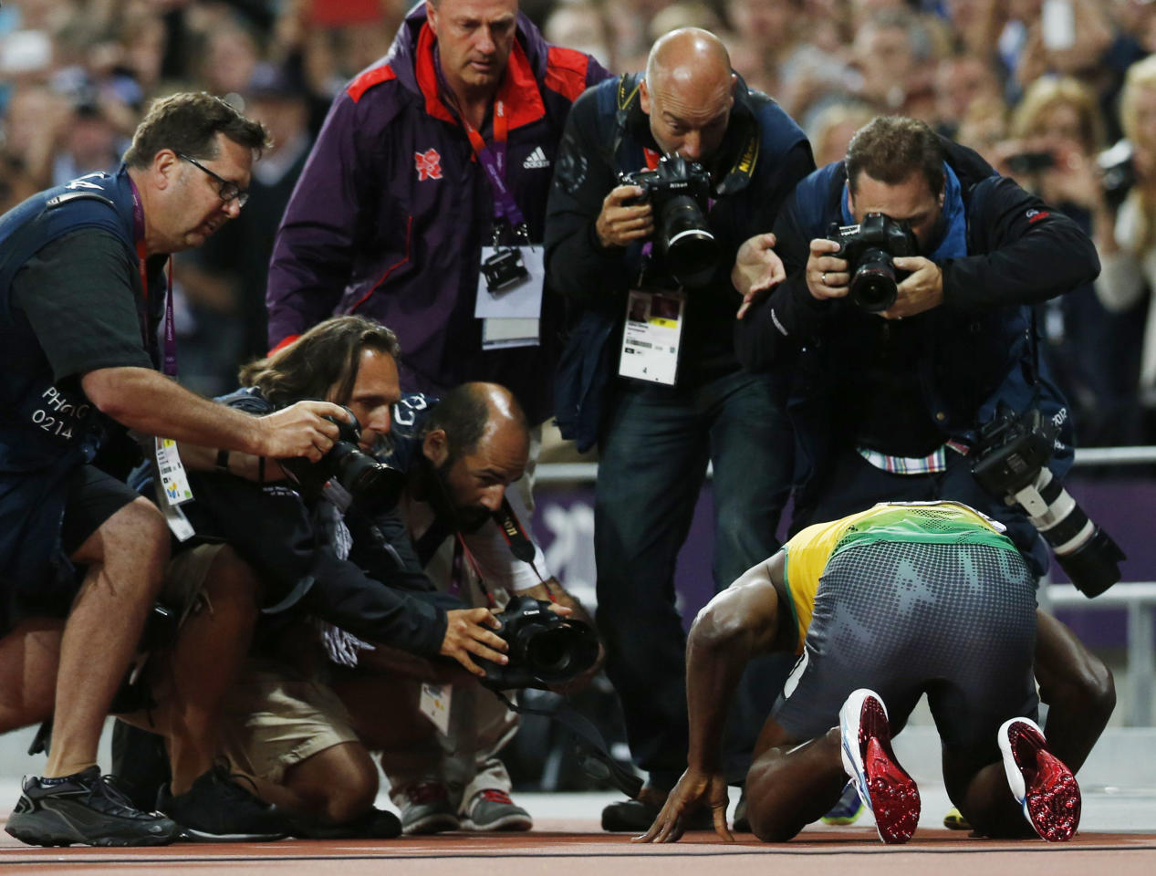 News photographers crowd around Jamaica's Usain Bolt as he celebrates victory after the men's 100m final during the London 2012 Olympic Games at the Olympic Stadium August 5, 2012.  REUTERS/Mark Blinch (BRITAIN  - Tags: OLYMPICS SPORT ATHLETICS)