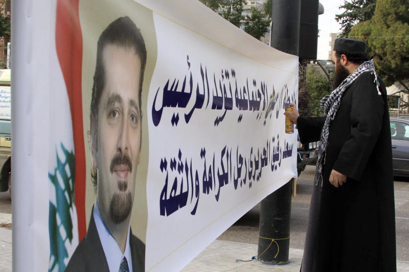 Pro-Hezbollah Lebanese Sunni cleric Suheb Habli, sprays his family name out of a banner supporting caretaker Prime Minister Saad Hariri, in the southern port city of Sidon, Lebanon, Tuesday, Jan. 18, 2011. Hezbollah supporters gathered in the streets of Beirut early Tuesday after a U.N. tribunal filed indictments in the assassination of a former prime minister, prompting several schools to close as nervous parents pulled their children from class. (AP Photo/Mohammed Zaatari)