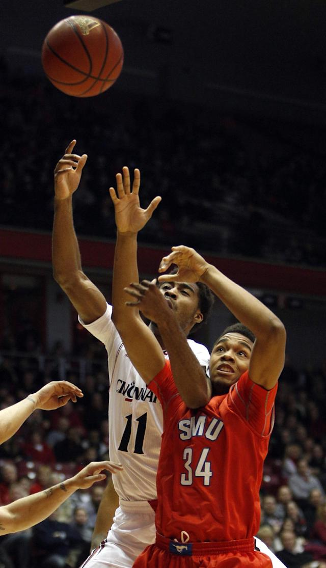 Cincinnati forward Jermaine Lawrence (11) and SMU forward Ben Moore (34) vie for the ball during the first half of an NCAA college basketball game, Wednesday, Jan. 1, 2014, in Cincinnati. (AP Photo/David Kohl)
