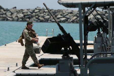 A member of the U.S. Navy Fifth Fleet prepares to escort journalists to the Japanese-owned Kokuka Courageous tanker at a U.S. NAVCENT facility near the port of Fujairah, United Arab Emirates